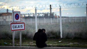Un menor frente a la valla que separa el campo de la carretera al puerto. Fuente: The Guardian